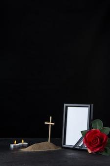 Vista frontal de la pequeña tumba con cruz y marco de imagen en negro