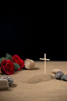 Vista frontal de la pequeña tumba con flores rojas y piedras de la guerra de israel