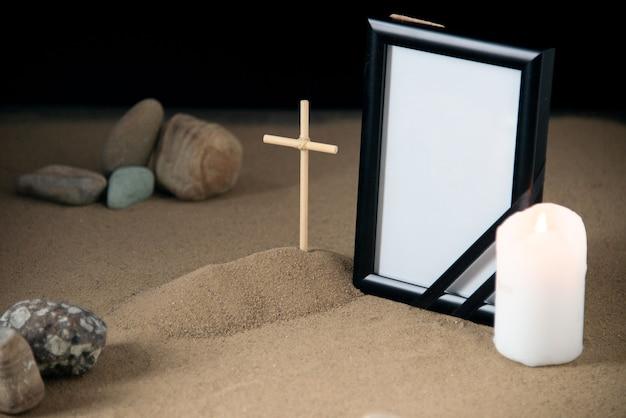 Vista frontal de la pequeña tumba con marco de fotos de piedras y velas