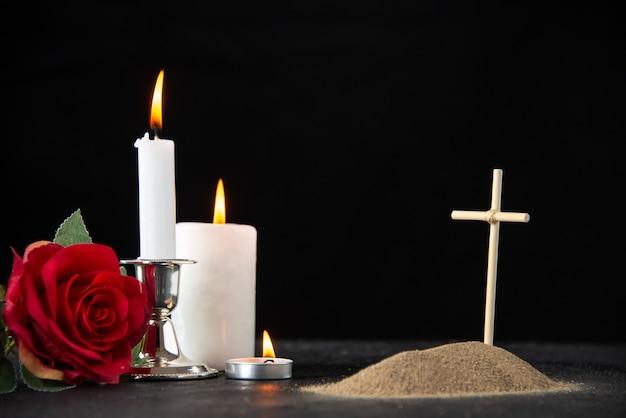 Vista frontal de la pequeña tumba con rosa roja y velas en negro