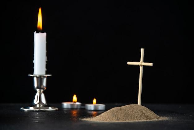 Vista frontal de la pequeña tumba con vela en negro