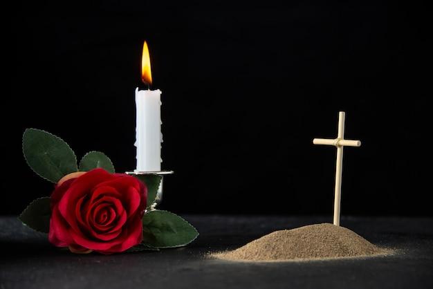 Vista frontal de la pequeña tumba con vela y rosa sobre negro