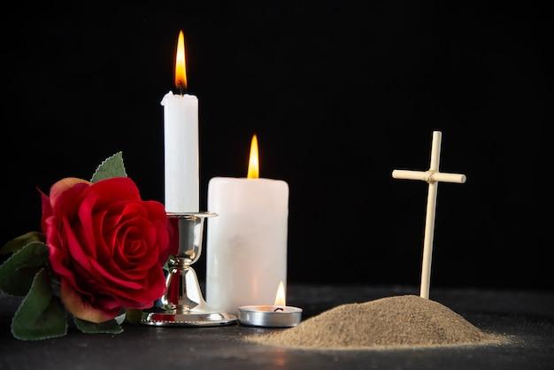 Vista frontal de la pequeña tumba con velas en el negro