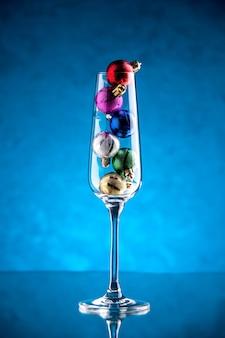 Vista frontal pequeñas bolas de navidad en copa de vino sobre superficie azul