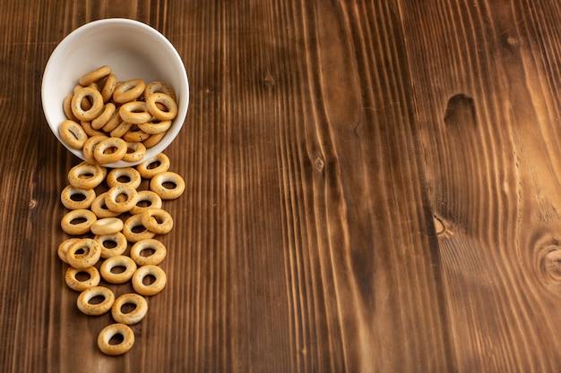 Vista frontal pequeñas galletas dentro de la placa sobre superficie de madera