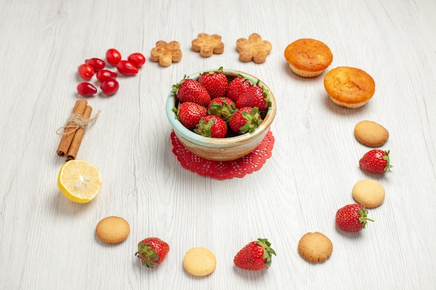 Vista frontal pequeñas galletas con frutas frescas en el escritorio blanco galleta galleta té dulce