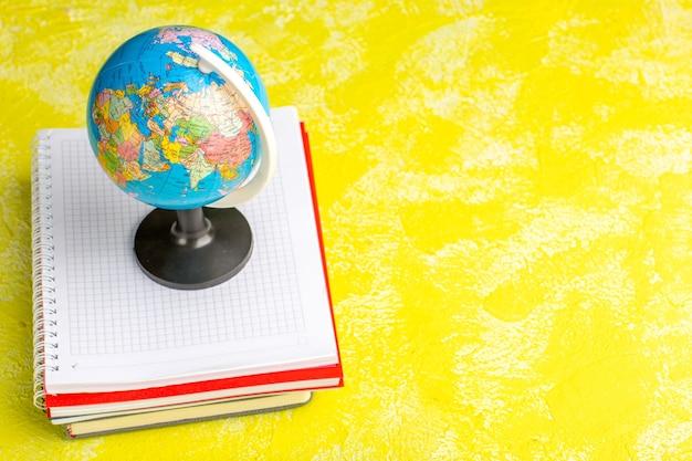 Vista frontal del pequeño globo con cuadernos sobre superficie amarilla