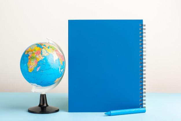 Vista frontal pequeño globo terráqueo con cuaderno azul sobre escritorio azul