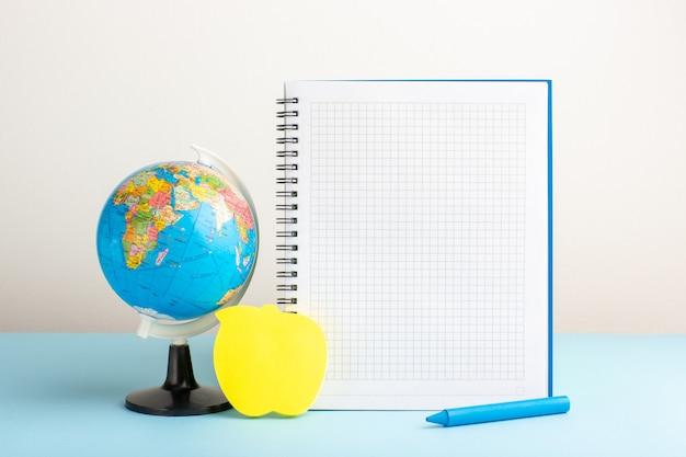 Vista frontal pequeño globo terráqueo con cuaderno sobre escritorio azul
