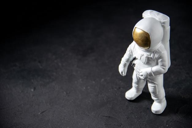 Vista frontal del pequeño juguete del astronauta en el negro