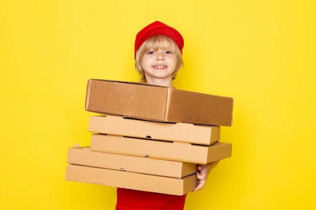 Una vista frontal pequeño mensajero lindo en camiseta roja gorras rojas jeans posando sosteniendo cajas de pizza marrón
