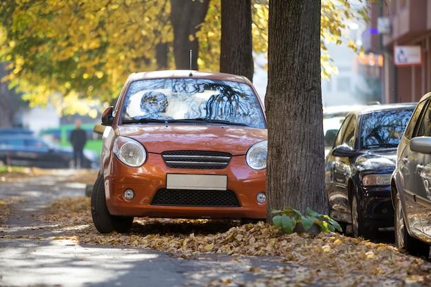 Vista frontal del pequeño mini automóvil naranja estacionado en un patio tranquilo en un soleado día de otoño en edificios borrosos y grandes árboles viejos follaje dorado fondo bokeh.