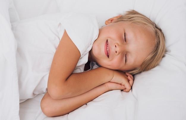 Vista frontal pequeño niño que tiene dulces sueños