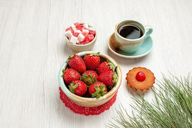 Vista frontal pequeño pastel con frutas y una taza de té en el escritorio blanco pastel de frutas postre de té