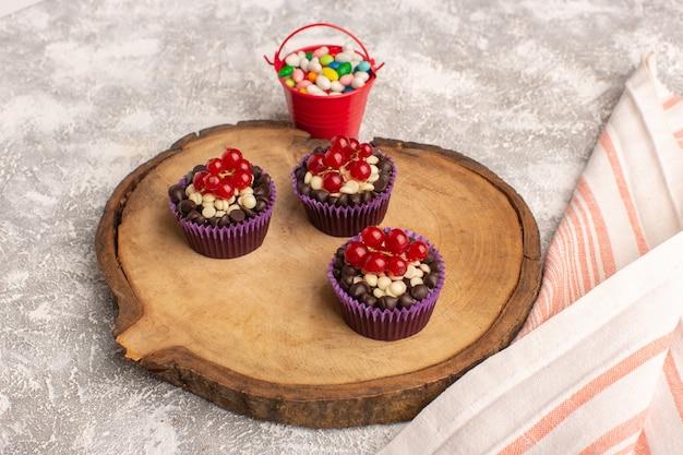Vista frontal de pequeños brownies de chocolate con arándanos y dulces