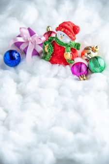 Vista frontal pequeños juguetes de árbol de navidad de muñeco de nieve sobre superficie blanca aislada