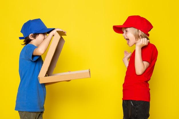 Una vista frontal pequeños mensajeros lindos en camisetas rojas y azules gorras rojas y azules jeans