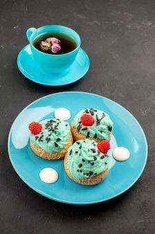 Vista frontal de pequeños pasteles cremosos deliciosos dulces con una taza de té sobre el fondo oscuro color de postre de galletas de pastel de crema de té