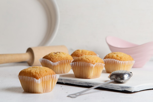 Vista frontal de pequeños pasteles deliciosos con azúcar en polvo dentro de la placa con una cuchara en la superficie blanca