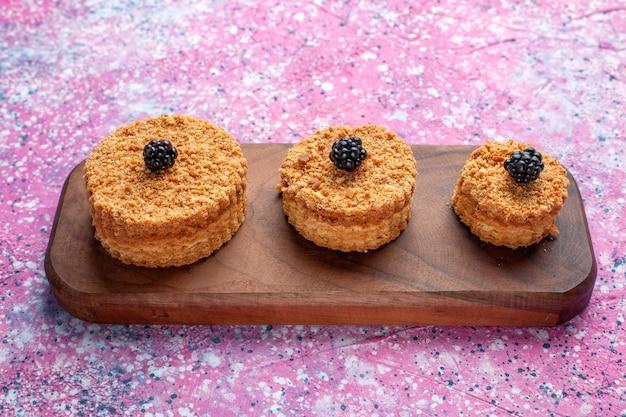 Vista frontal de pequeños pasteles deliciosos formados en la superficie rosada