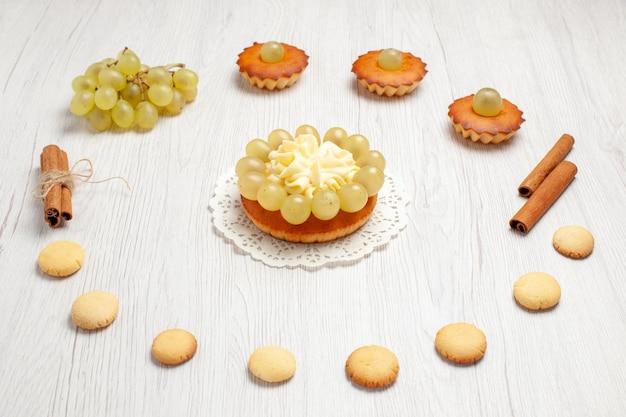 Vista frontal pequeños pasteles deliciosos con uvas y galletas en el escritorio blanco pastel galleta postre dulce galleta