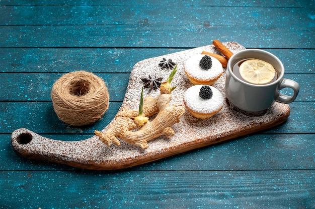 Vista frontal de pequeños pasteles con taza de té en un espacio azul rústico