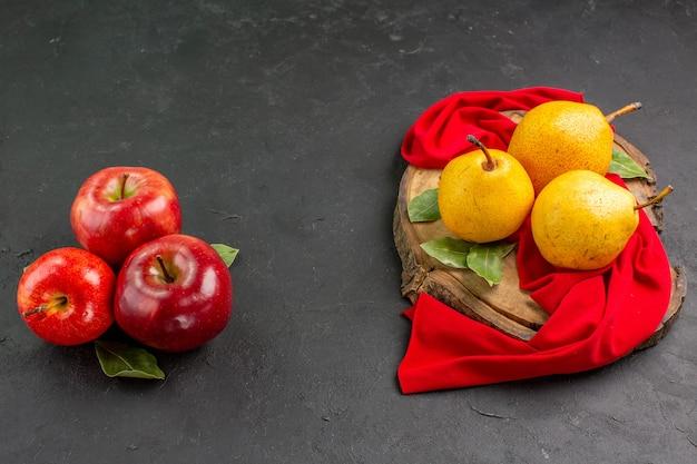 Vista frontal de peras dulces frescas con manzanas en el árbol de mesa gris suave maduro fresco