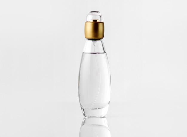 Una vista frontal de perfume dentro de la botella con tapa dorada en el blanco