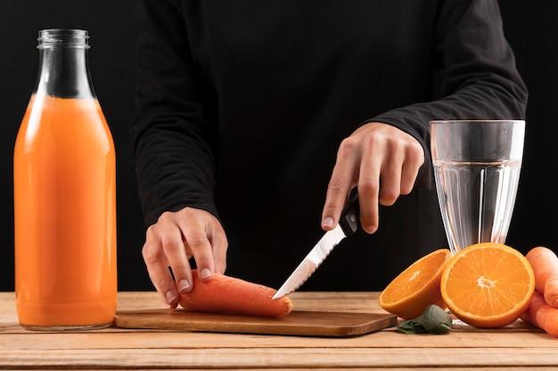 Vista frontal persona cortando zanahorias cerca de batido