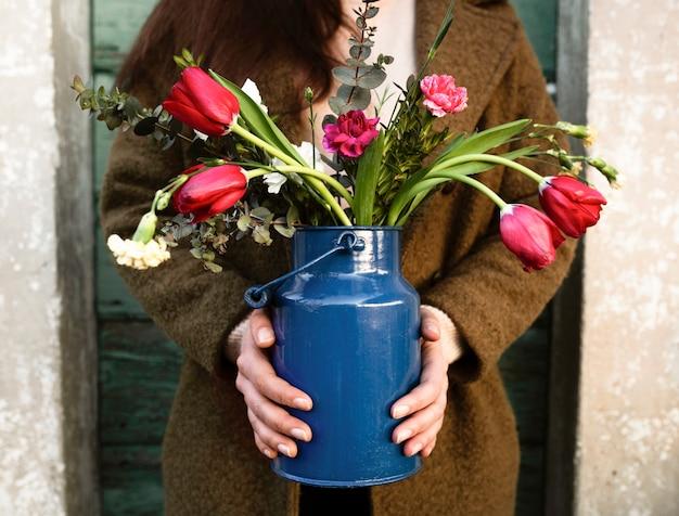 Vista frontal persona con jarrón de flores