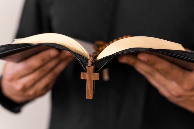Vista frontal de la persona con libro sagrado y rosario