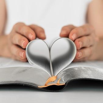 Vista frontal de la persona que hace el corazón de las páginas del libro sagrado