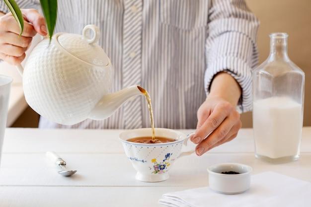 Vista frontal de la persona que prepara té con leche