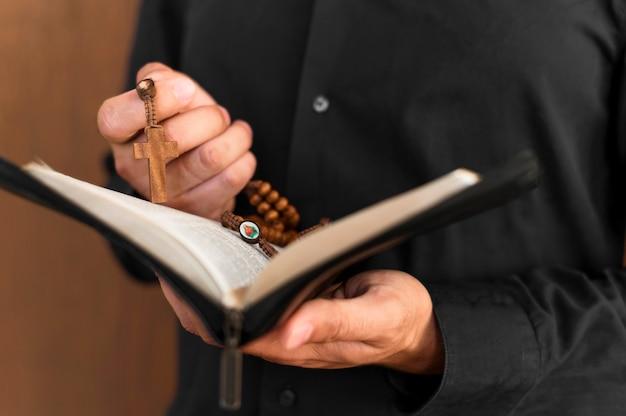 Vista frontal de la persona que sostiene el libro sagrado y el rosario