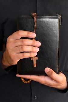Vista frontal de la persona que sostiene el libro sagrado con rosario