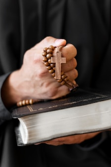 Vista frontal de la persona que sostiene el rosario con la cruz y el libro sagrado