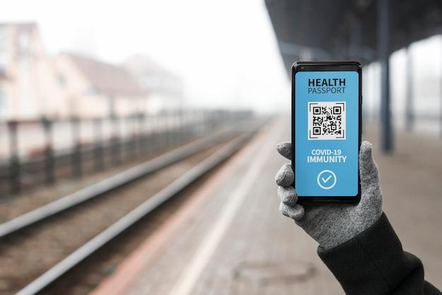 Vista frontal de la persona que tiene un pasaporte de salud virtual en un teléfono inteligente