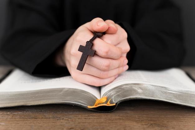 Vista frontal de la persona rezando con cruz y libro sagrado