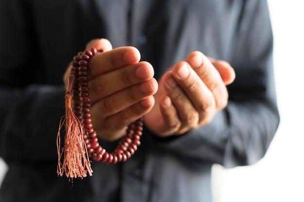 Vista frontal de la persona rezando con rosario