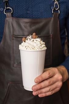 Vista frontal persona sosteniendo la taza llena de crema
