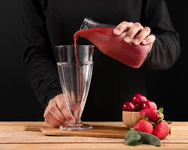 Vista frontal persona vertiendo batido en vaso cerca de frutos rojos