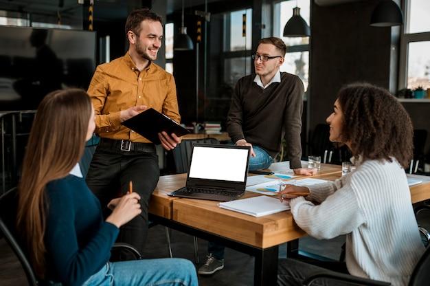 Vista frontal de personas con laptop y papeles durante una reunión en la oficina