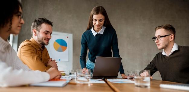Vista frontal de personas con laptop y papeles durante una reunión