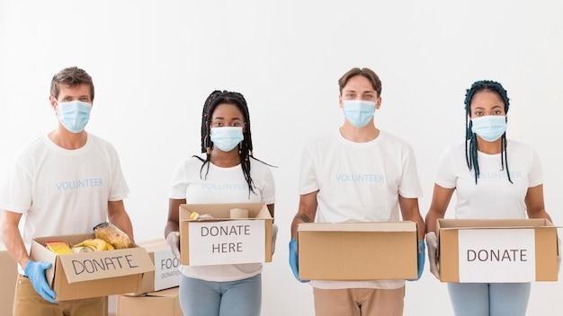 Vista frontal de personas preparando paquetes de donaciones.