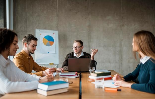 Vista frontal de personas que tienen una reunión en la oficina.