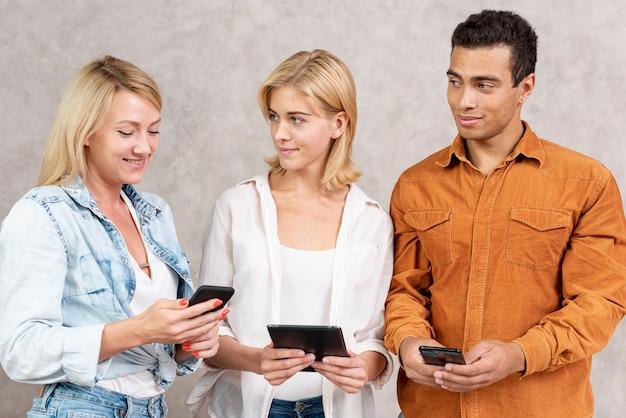Vista frontal de personas que usan sus teléfonos
