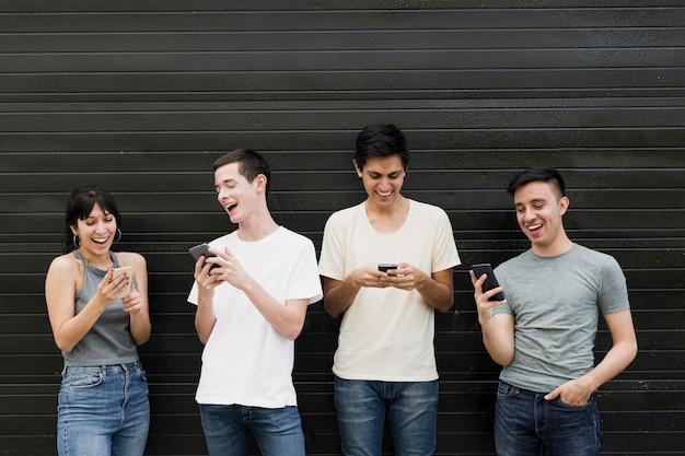 Vista frontal de personas con teléfonos móviles
