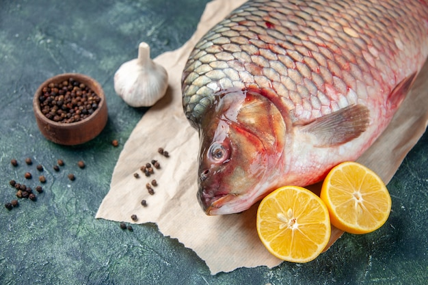 Vista frontal pescado crudo fresco con pimienta y limón en superficie azul oscuro carne agua océano color comida horizontal comida de mariscos