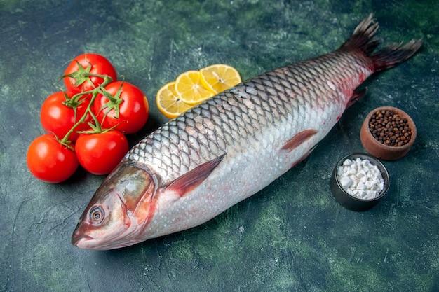 Vista frontal pescado crudo fresco con tomates y rodajas de limón en la superficie azul oscuro tiburón mariscos comida del océano carne del océano cena horizontal color de los alimentos agua animal