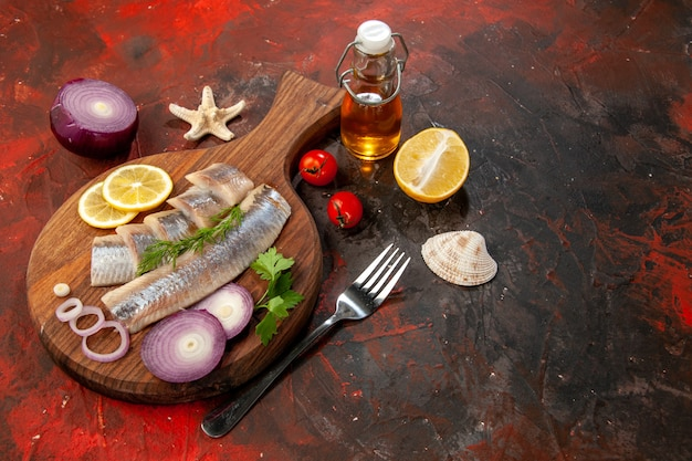 Vista frontal de pescado crudo en rodajas con aros de cebolla sobre carne de ensalada de color marisco oscuro